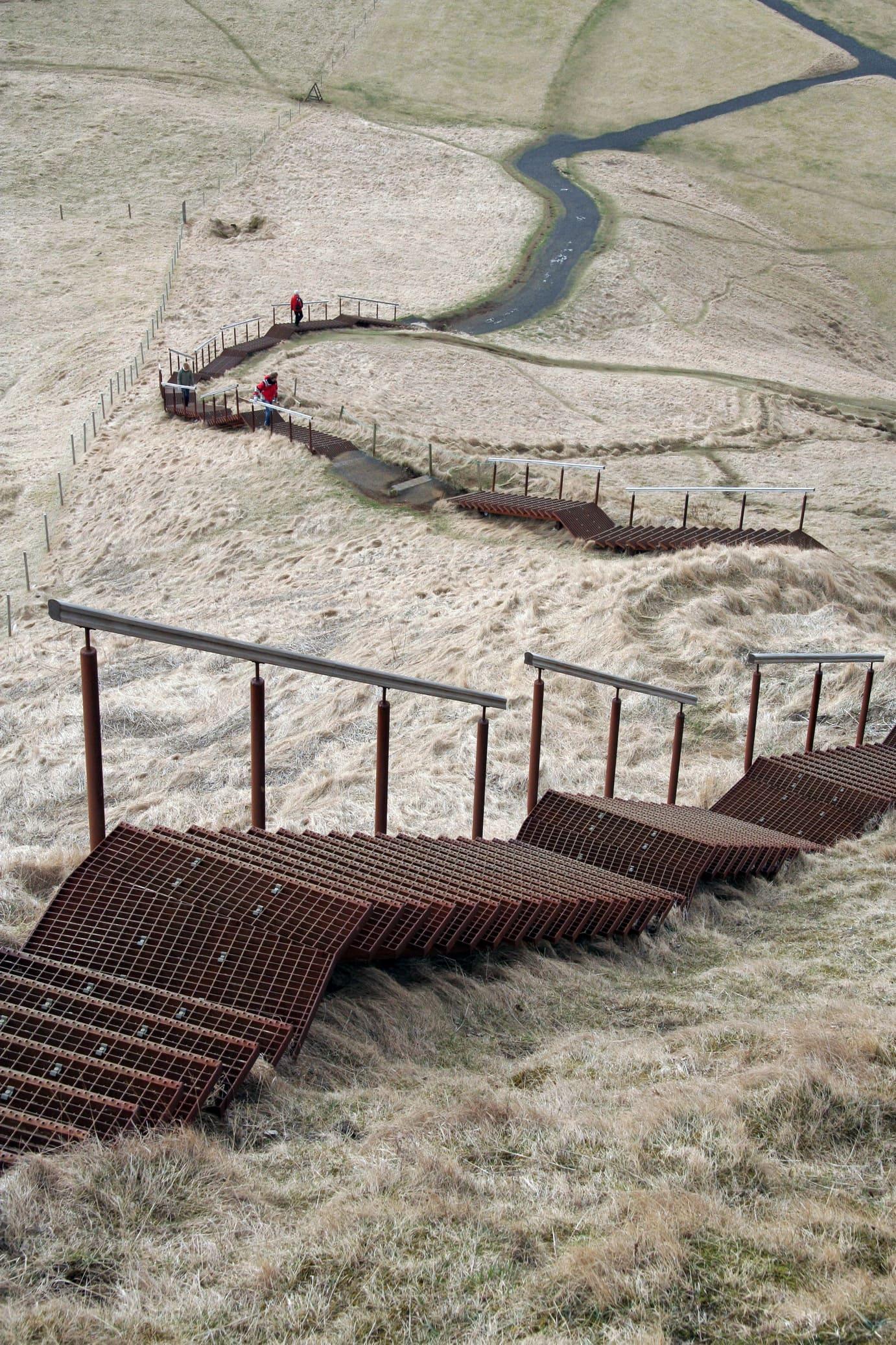 На вершину утеса, с которого падает водопад, ведет лестница