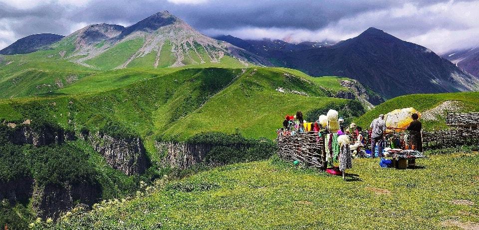 Торговцы предлагают сувениры, горный мед, кавказские шапки